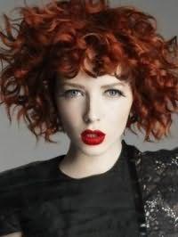 Дневной макияж с акцентом на ярко-красных губах идеально смотрится с укладкой волос рыжего оттенка в виде мелких локонов