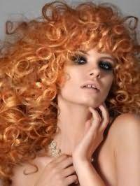 Макияж глаз в стиле смоки айс гармонирует с макияжем губ в натуральных тонах и дополняет вечерний образ девушки со светло-рыжими длинными волосами, уложенными в мелкие локоны