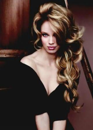 Длинные волосы с крупными пышными локонами с мелированием гармонируют с вечерним макияжем, состоящим из темно-коричневых теней, персиковых румян и помады бордового оттенка