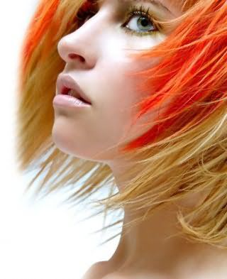 Короткая рваная стрижка для блондинок великолепно гармонирует с мелированием яркого оранжевого оттенка и макияжем с черной тушью, розовыми румянами и блеском для губ натурального цвета