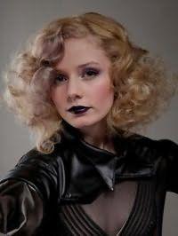 Русый цвет хорошо смотрится на стрижке каре на кудрявые волосы с челкой на один бок и сочетается с черной тушью, розовыми румянами и макияжем губ в черных тонах