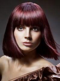 Гармоничное сочетание цвета волос красное дерево со стрижкой удлиненное каре с рваными концами и густой прямой челкой идеально дополняется макияжем глаз в коричневых оттенках и розовой помадой