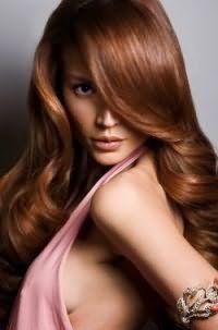 Длинные волосы цвета золотистый каштан с укладкой в виде крупных пышных локонов на стрижке лесенка гармонично дополнят образ в сочетании с макияжем в коричневых тонах для обладательниц черных глаз